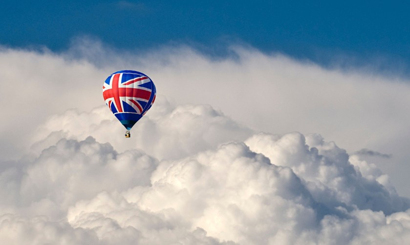 A hot air Balloon with a Union flag motif flying in front of dramatic storm clouds